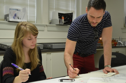 Photo of Brian Taylor and a student, working on designs